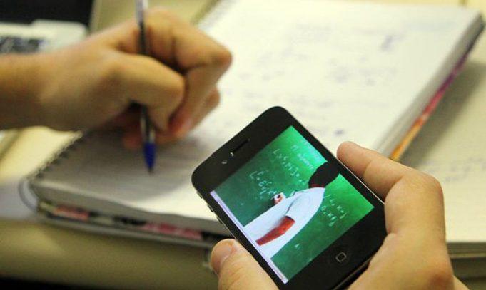 Estudante com caderno e videoaula no celular